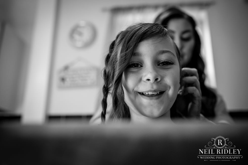 Manchester Wedding Photographer black and white image of young flower girl having her hair plaited