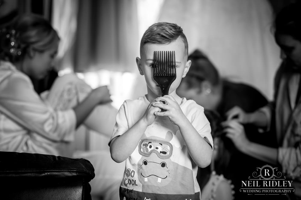 Manchester Wedding Photographer  black and white image of page boy stood holding a  comb over his face