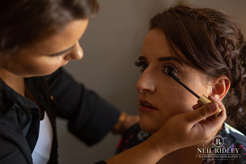 Manchester Wedding Photographer bridesmaid having mascara applied by mua