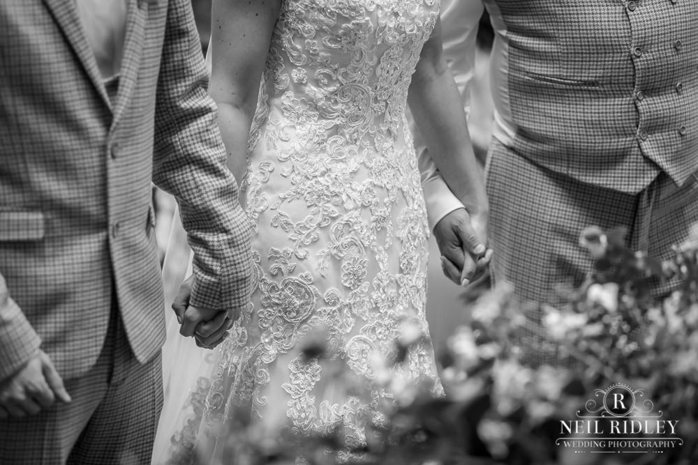 Wyresdale Park Wedding - Bride holding Groom and Fathers hands
