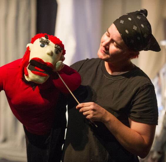 Theatre student performing with a puppet.