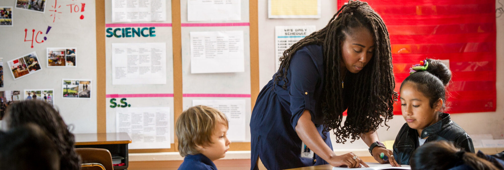 Female elementary school teacher interacting with a young boy and girl in classroom.
