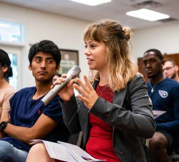 Student speaking holding a speaker.