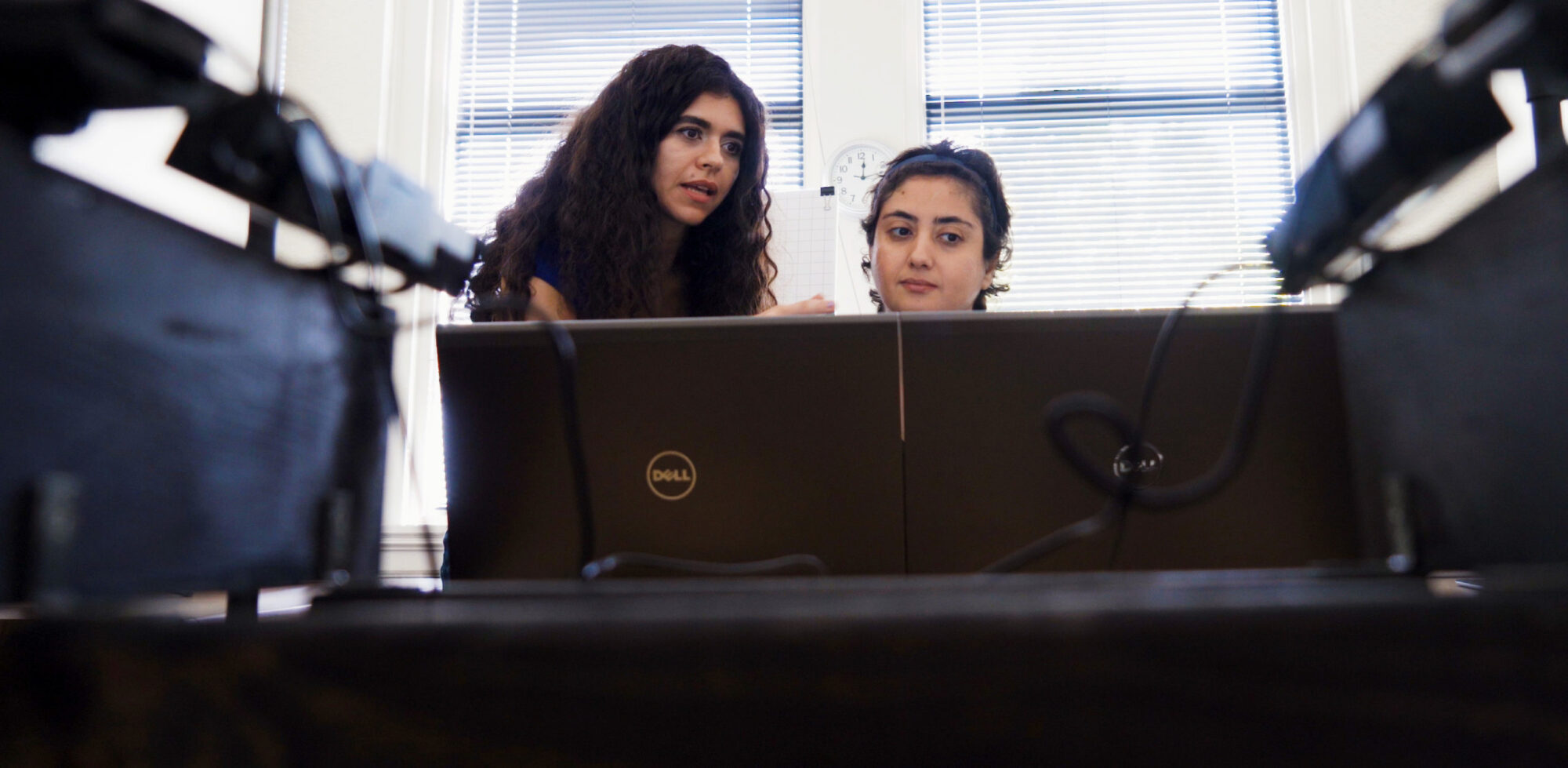 Two females, one is teaching the other something about the computer.