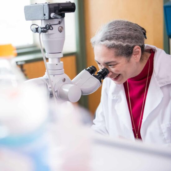 Scientist looking into microscope in Biology lab