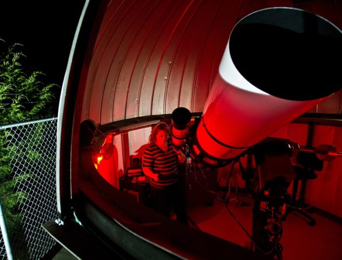Students viewing stars with giant telescope.