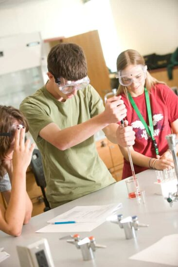 Student experiment in biology lab with two other students