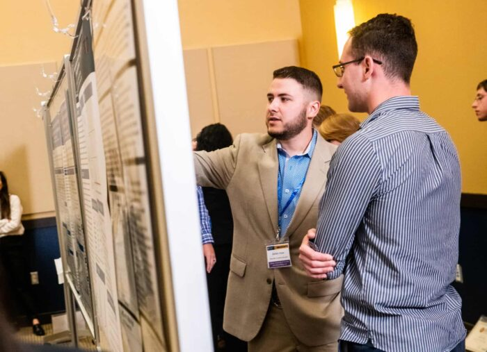 Two individual having a conversation during the annual Research Symposium.