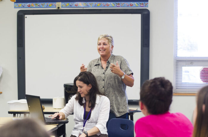 Teacher instructing a group in a classroom.