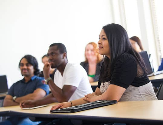 Students in class sitting down at desks listening to lecture.