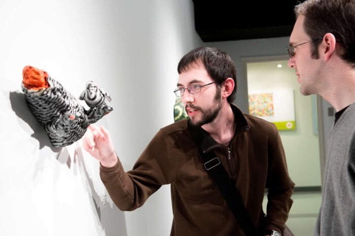 Two men reviewing 3 dimensional art piece hanging on wall.