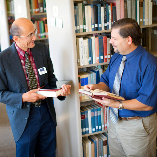 Two male professor in the library taking with books in their hands.