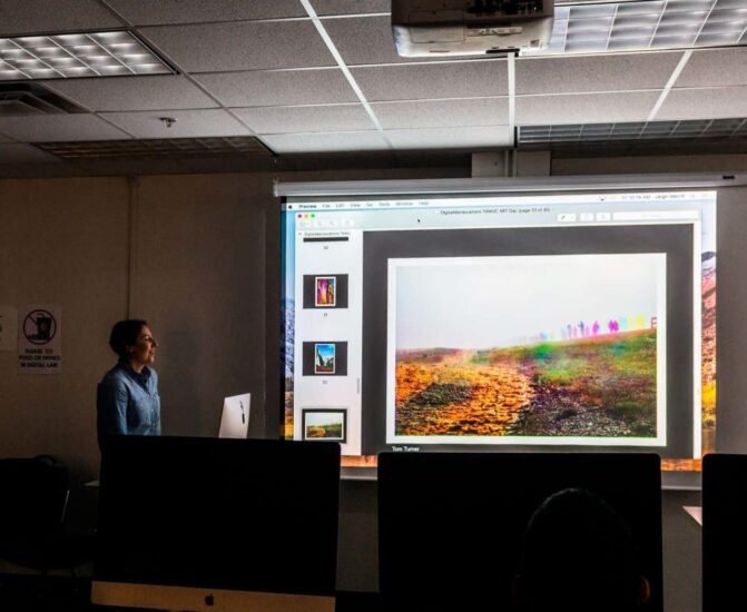 Instructor teaching course in dark class with projector.