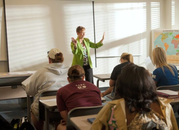 Female teacher instructing college students in classroom.