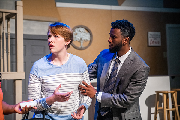 Two actors during a scene. One dressed in a suit, the other one wearing a striped long sleeve shirt.