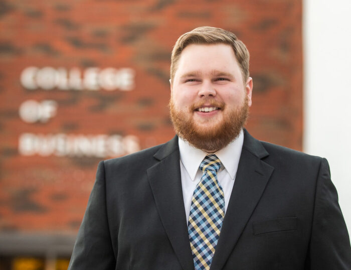 A gentlman by the name Chase Miller standing in front of the College of Business.