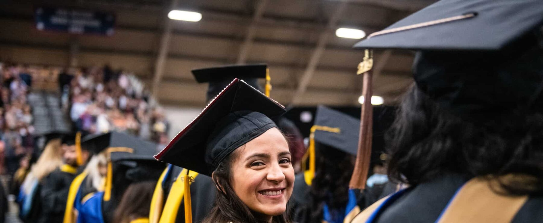 Graduate student smiling at the camera during graduation.