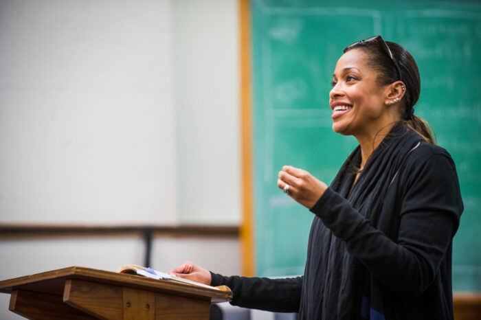 A female educator with big smile reading a poem to audience.