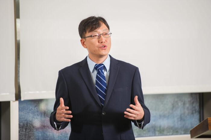 Man wearing suit and tie speaking.