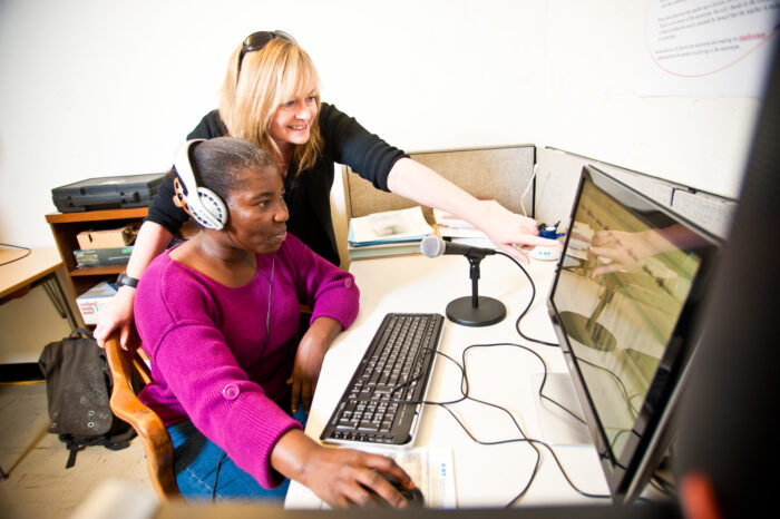 An educator teaching a student who is setting at a computer while wearing headphones.