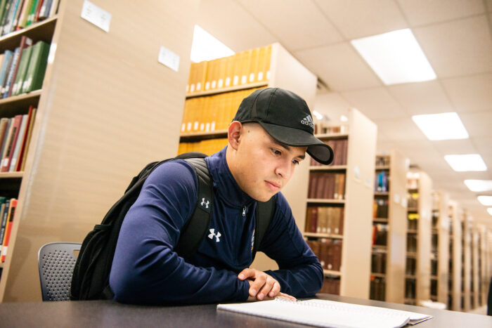 Male student reading a book in a library.