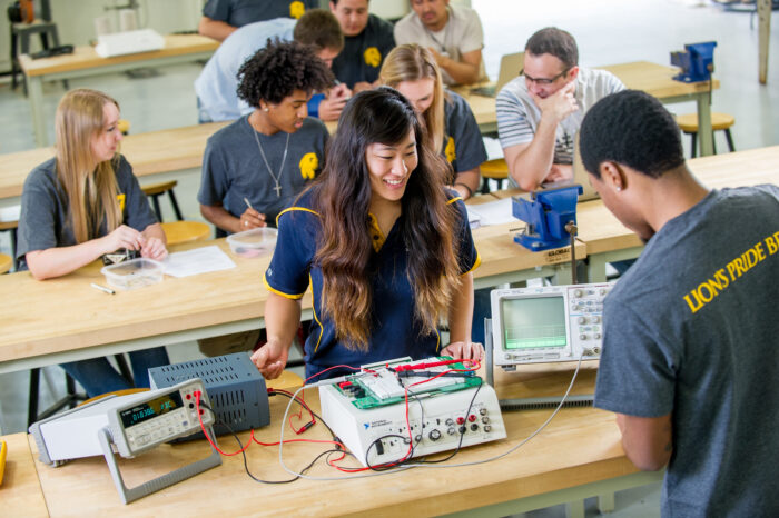 Science and Engineering students working on a circuit board.