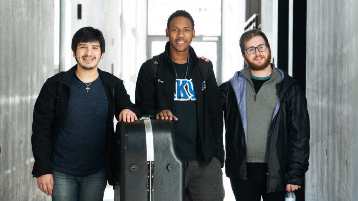 Three young men standing in hallway with large instrument in case
