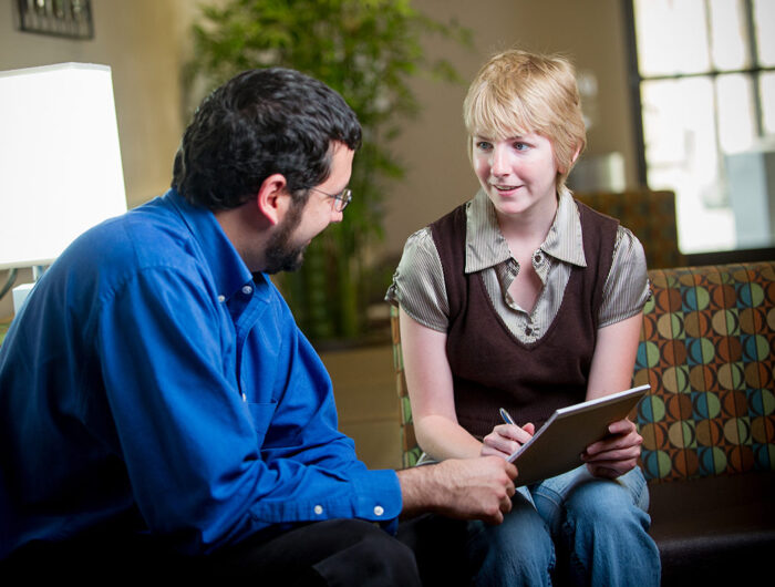 Woman counselor mentoring male student.