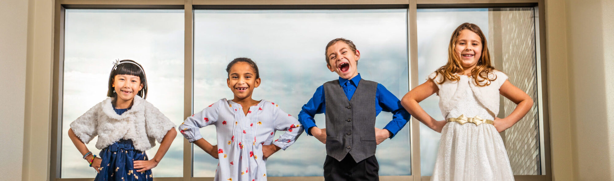 four kids standing in front of large windows standing tall and laughing.