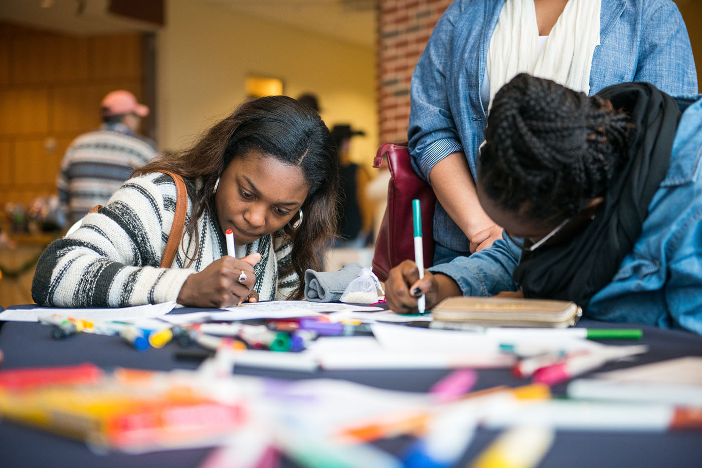 Two students coloring siting at a table.