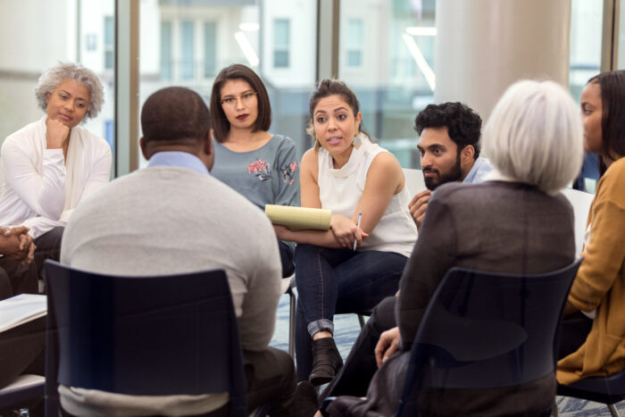 A group of people sitting down in a circle listening to a therapist.