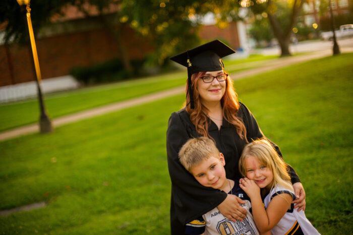 Graduate in cap and gown taking a picture with her kids.