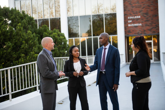A group of professors and students talking outside of the College of Business building.