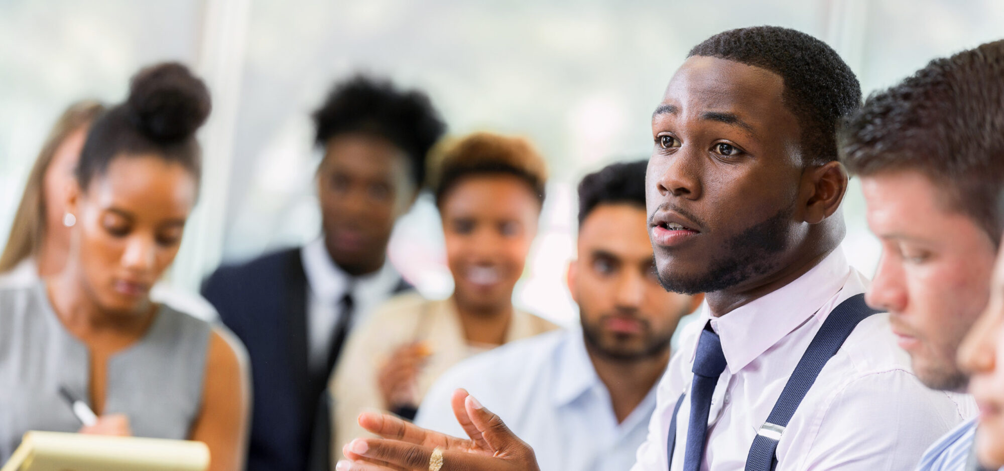 A serious young African American male business student talks with his hands as he sits at a table in a lecture hall and poses a question to an unseen professor. Other students sit in the audience in the background.