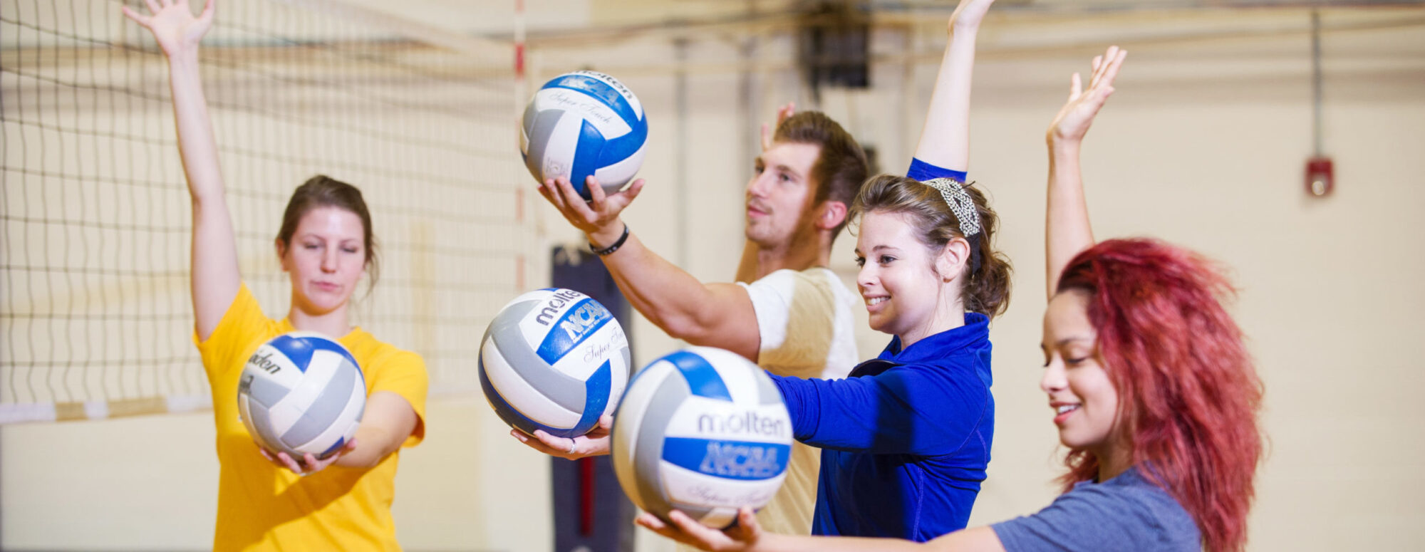 Young female volleyball player coaching one young man and two women
