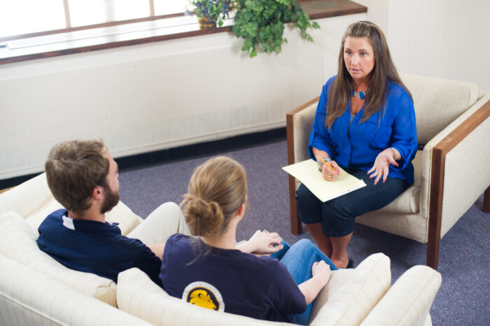 Counseling interacting with couple in couples counseling session.