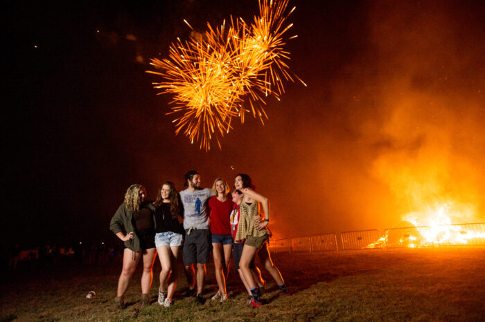 A group of students taking a photo with fireworks and a bonfire in the background.