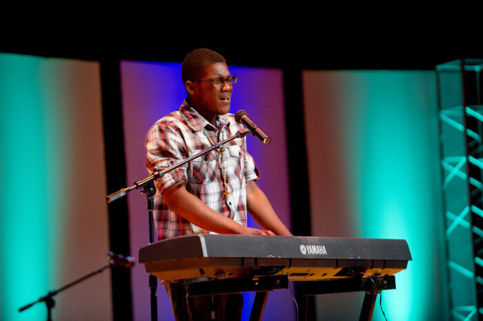 A student playing the piano and singing at a talent show.
