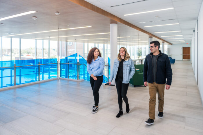 Three students walking in atrium space on second floor.