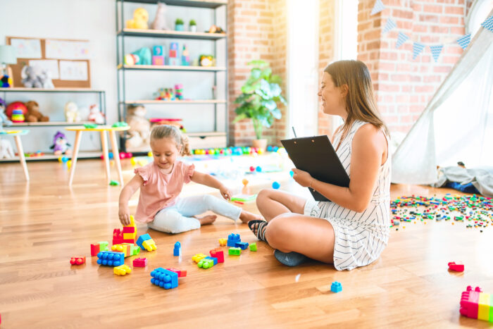 Psychologist and blond toddler girl doing therapy building tower using plastic blocks.