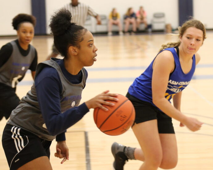 Three females students playing basketball.