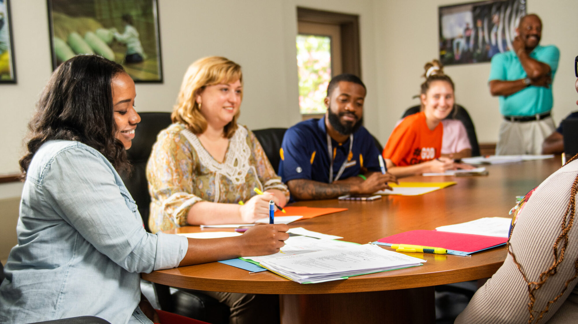 A group of educator and students sitting at a table.