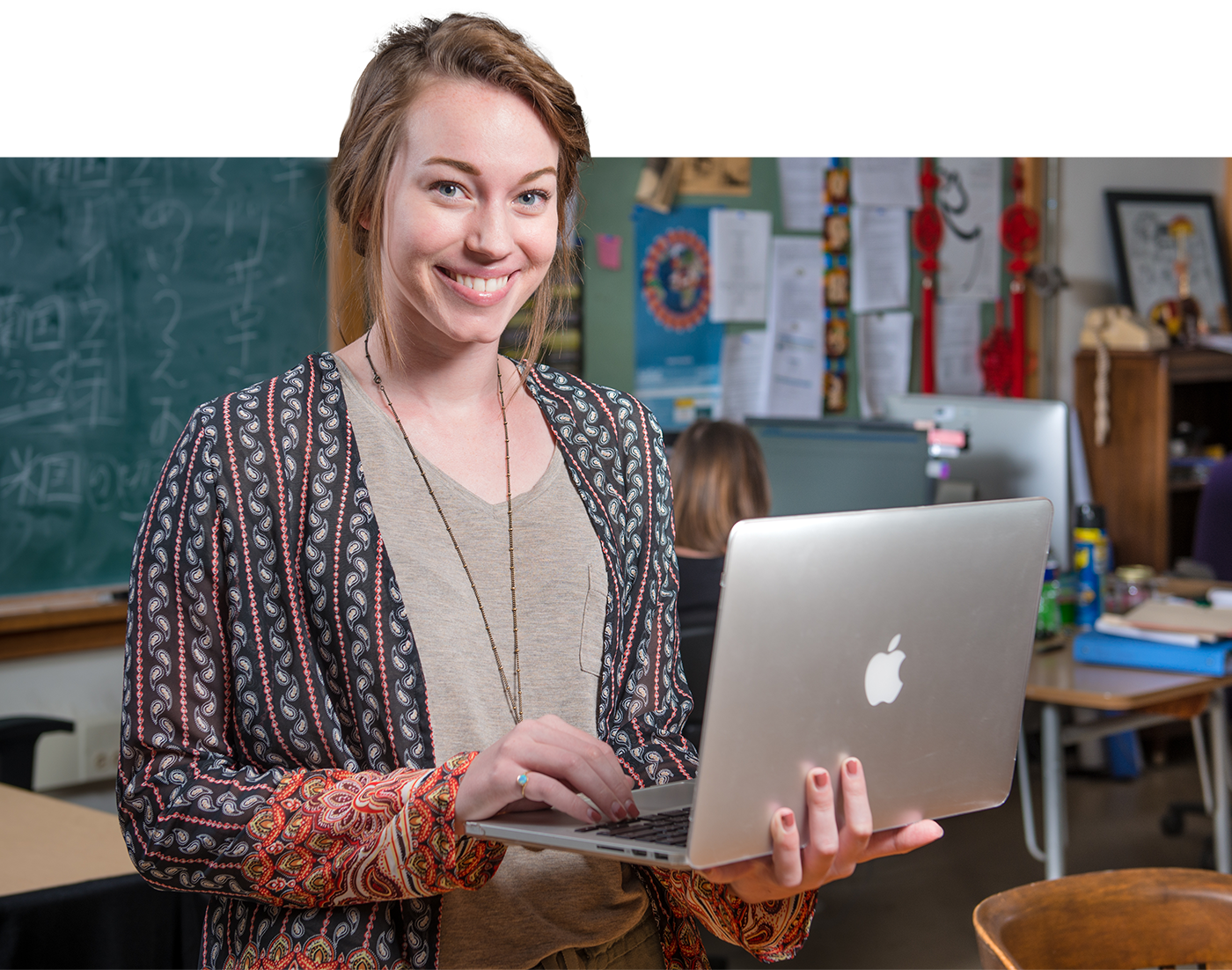 Student holding a laptop smiling at the camera.