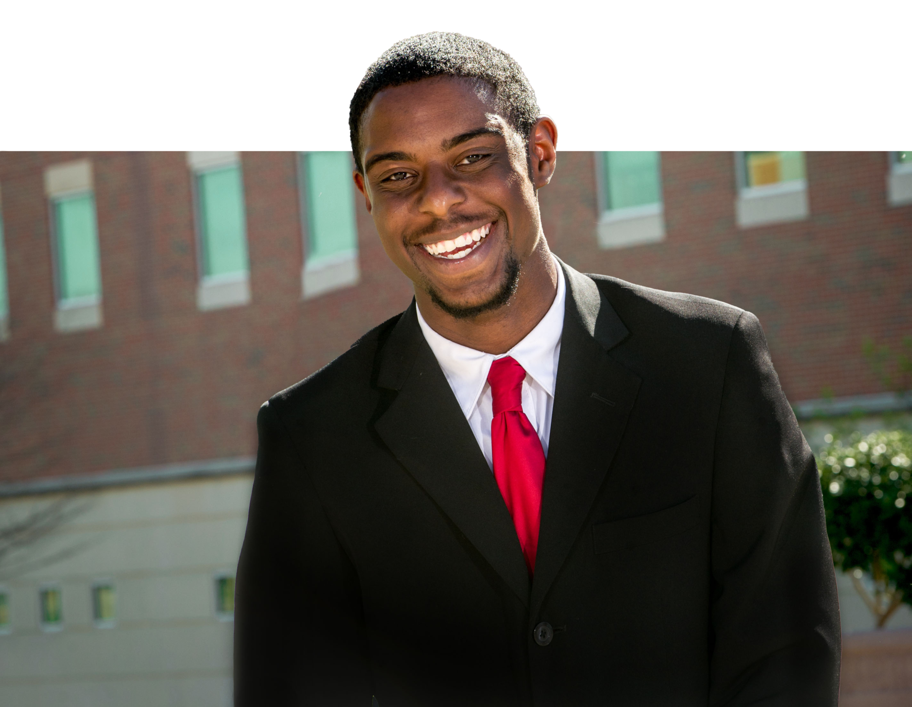 Student dressed professional smiling at the camera.