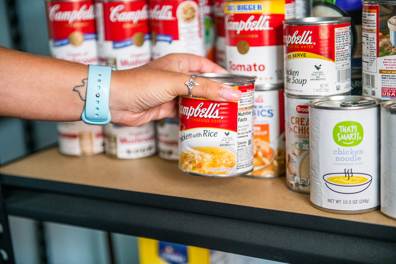 An individual grabbing a can of food from a shelf.