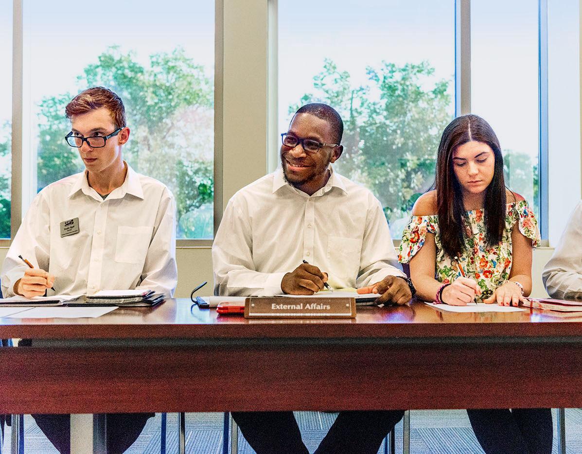 Three student siting at a desk during a SGA meeting.