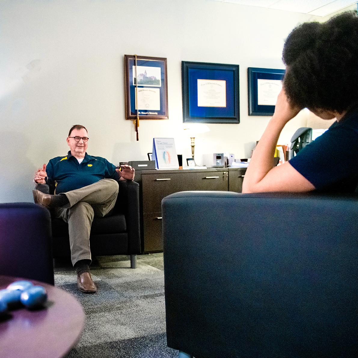 Counselor sitting down in a char talking to a student.