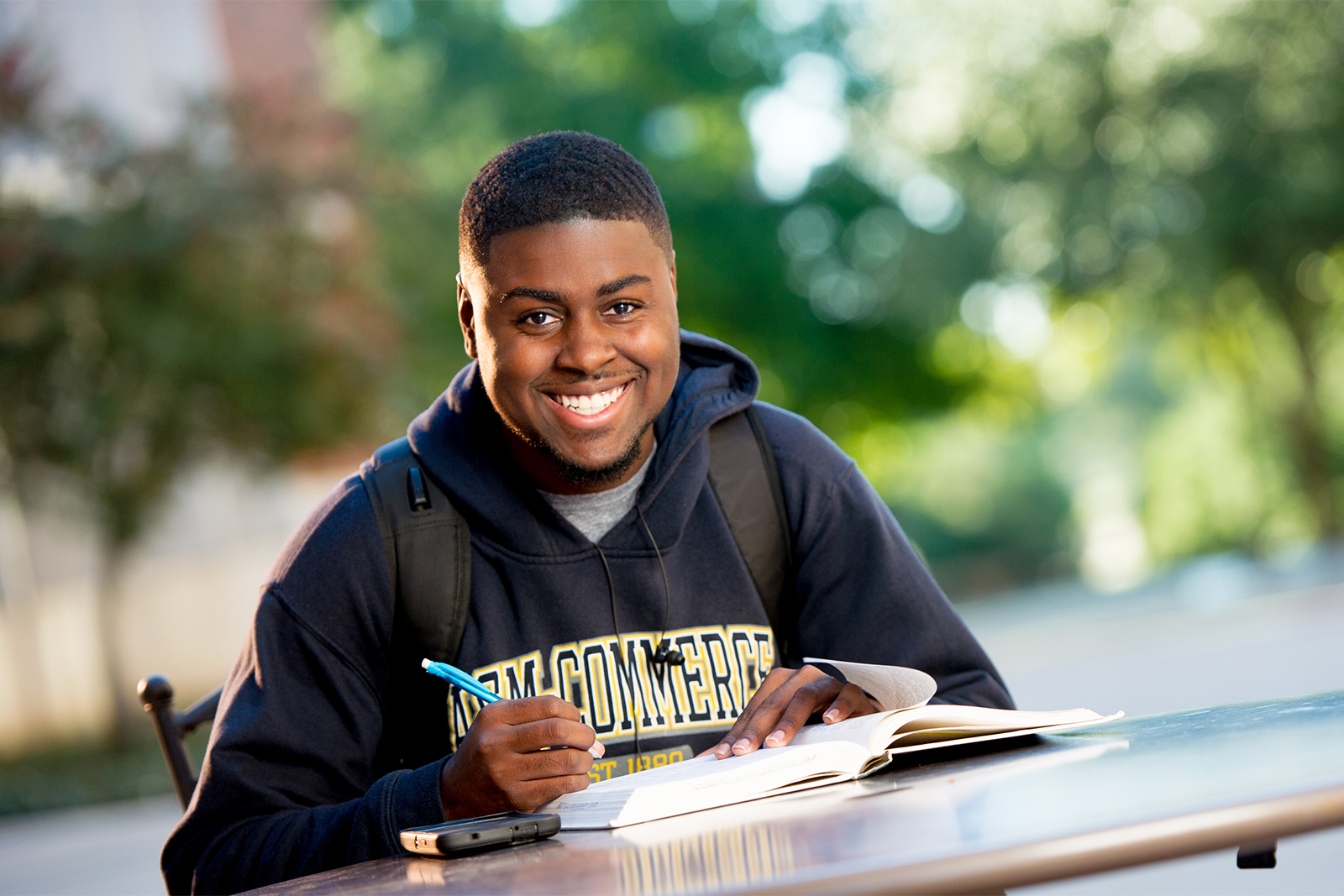 Student smiling siting at a outside table with book in front of him.