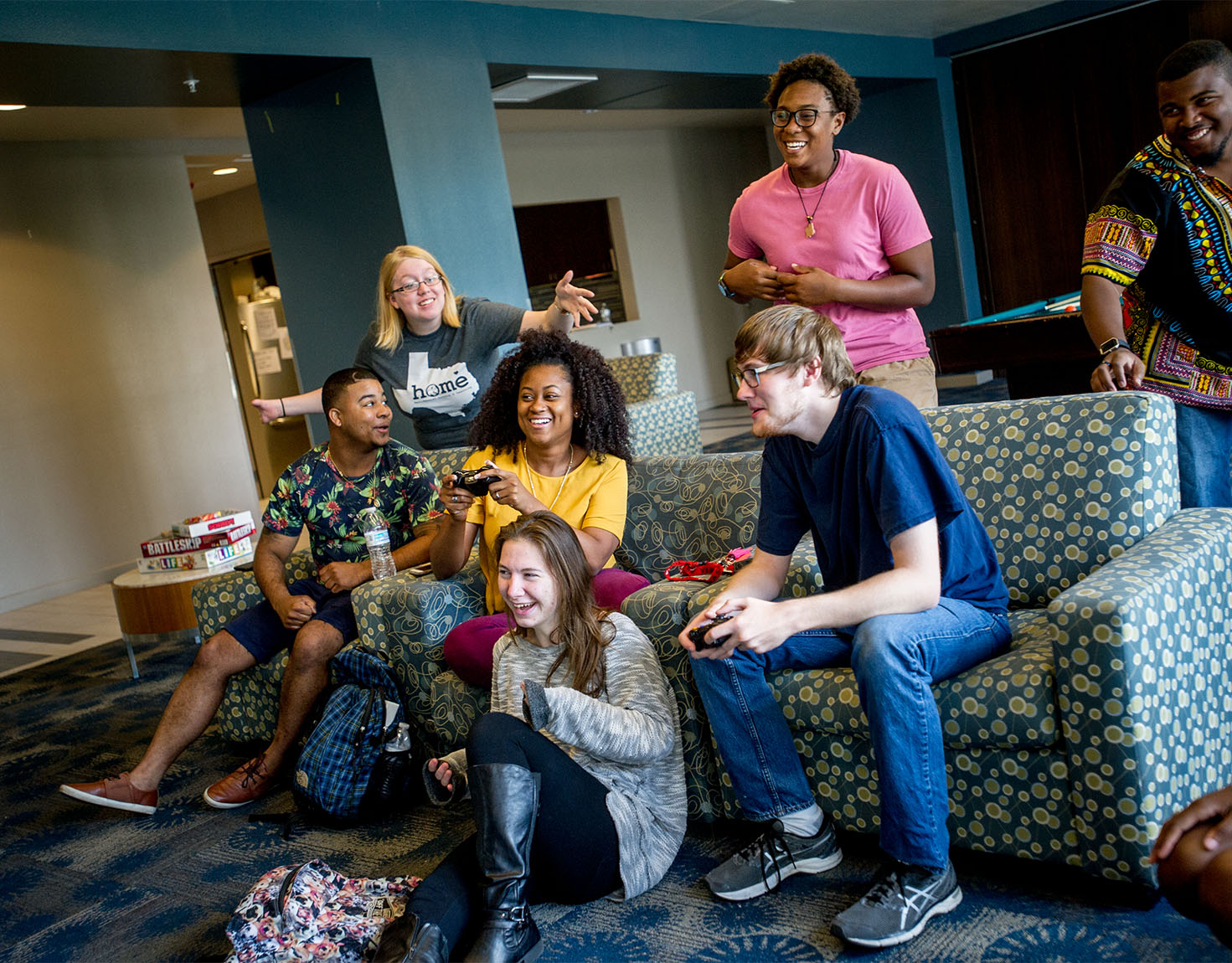 A group of student playing videogames and laughing.