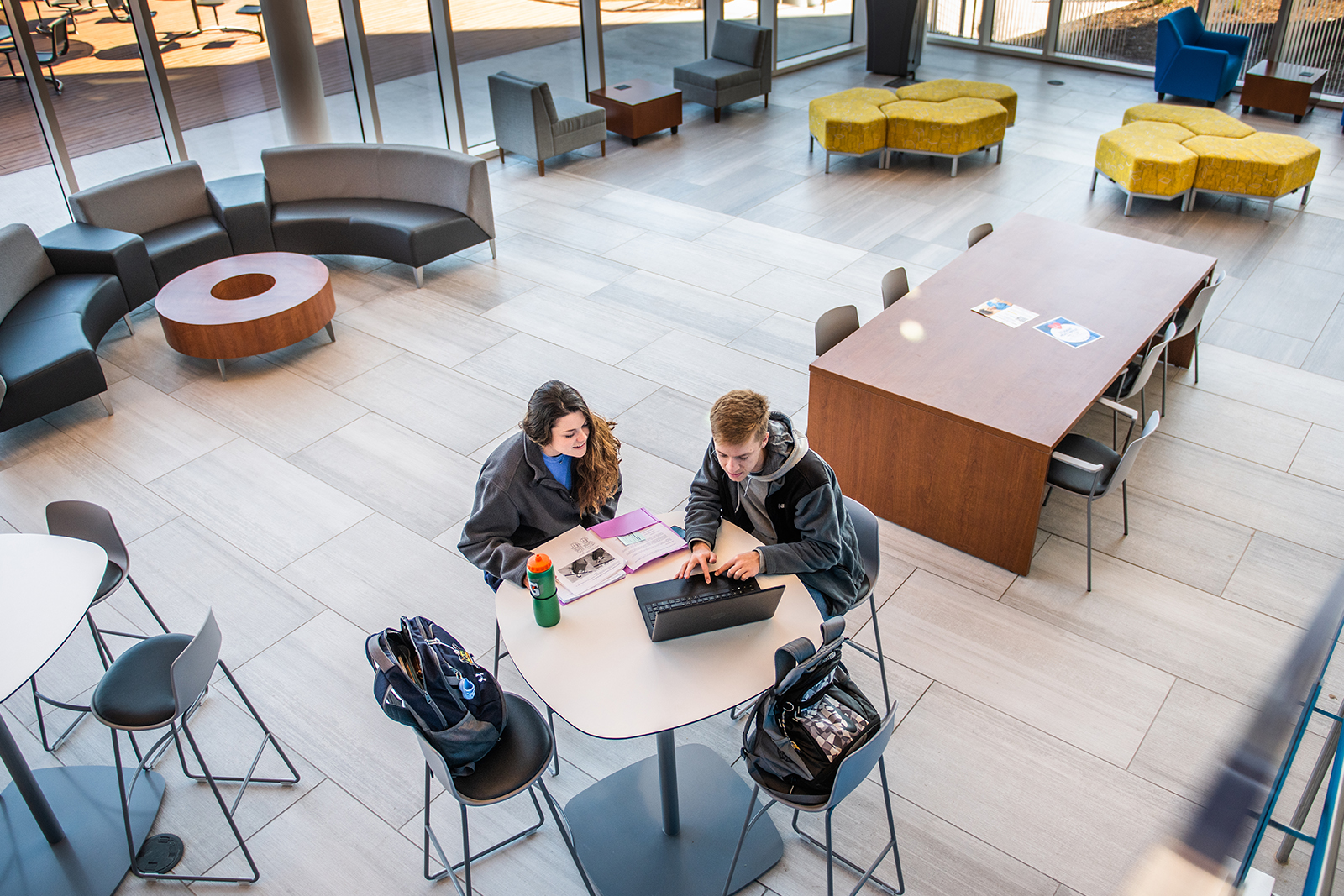 Two students siting at a table looking at a laptop in the new human sciences building.
